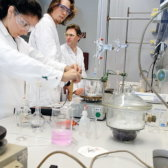 Female student and two male students in white coats and protective glasses working in a chemical laboratory.