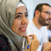 Student sitting smiling in an information class with application papers in hand.