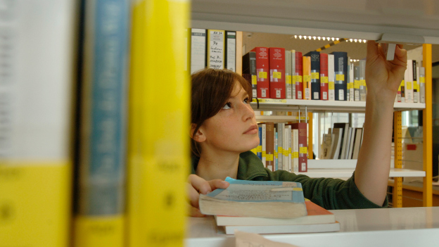 Student looking at books in the university library.