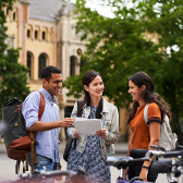 International students stand smiling in front of the University of Hanover with documents in hand.